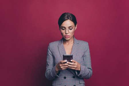 Portrait of her she nice cute attractive lovely sweet winsome classy chic focused concentrated lady wearing gray checkered jacket typing sms isolated over maroon burgundy marsala background