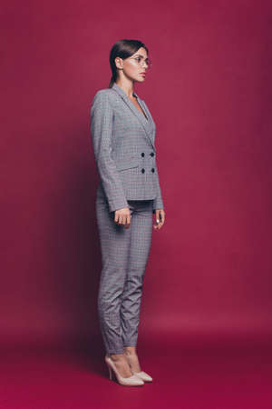 Vertical profile side half-turned full length body size view portrait of her she nice pretty attractive charming candid lady wearing gray suit isolated over maroon burgundy marsala pastel background