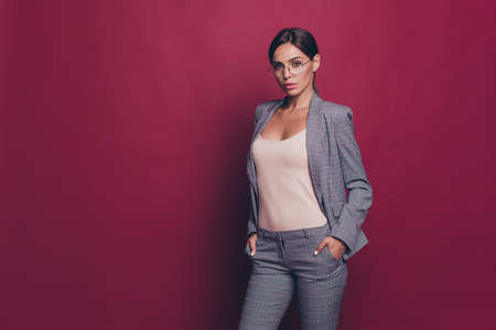 Portrait of her she nice cute attractive lovely sweet magnificent winsome shine classy content lady ceo boss chief leader wearing gray checkered suit isolated over maroon burgundy marsala background
