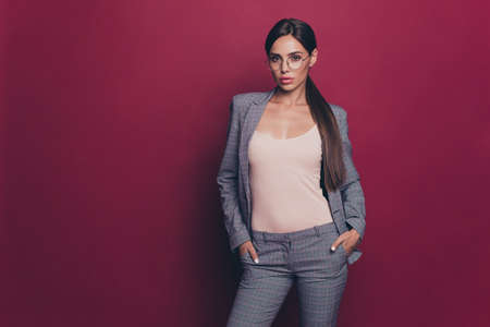 Portrait of her she nice cute attractive lovely lovable sweet magnificent winsome content lady wearing gray checkered suit trend life lifestyle isolated over maroon burgundy marsala background Stock Photo