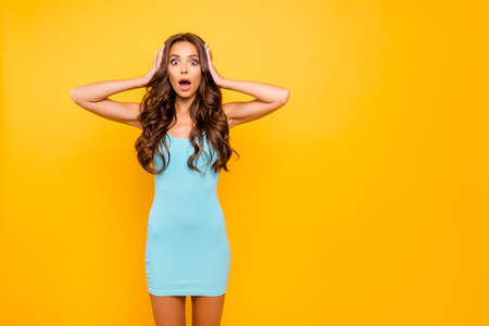 Close up photo amazing beautiful her she funky lady mouth eyes opened unbelievable arms hands hold head epic fail oh no wear blue teal green everyday short dress clothes isolated yellow background 免版税图像
