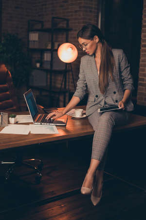 Vertical close up photo attentive she her business lady chief checking look e-reader e-book report information learn study compare analyze sit office table wear specs formal wear checkered suit