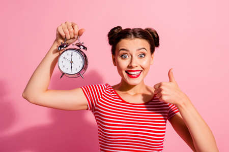 Close-up portrait of her she nice cute charming winsome attractive glamorous cheerful girl wearing striped t-shirt holding in hand showing clock thumbup hour isolated over pink pastel background Banque d'images - 119452879