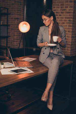 Vertical close up photo attentive she her business lady chief checking look notebook hold hot beverage information learn study compare analyze sit office table wear specs formal wear checkered suit