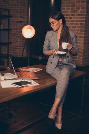 Verticale ravvicinata foto attenta lei la sua donna d'affari capo controllo guarda taccuino tenere bevanda calda informazioni imparare studiare confrontare analizzare sedersi ufficio tavolo indossare specifiche abbigliamento formale abito a scacchi Archivio Fotografico