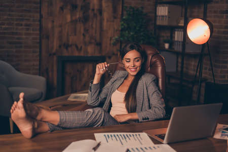 Close up side profile photo beautiful she her business lady chief hard week weekend speak legs table look satisfied notebook overjoyed sit office chair wear specs formal wear checkered suit Foto de archivo