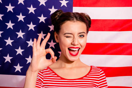 Close-up portrait of her she nice cute charming attractive glamorous girlish cheerful optimistic girl wearing striped t-shirt showing ok-sign cool good isolated over american flag background