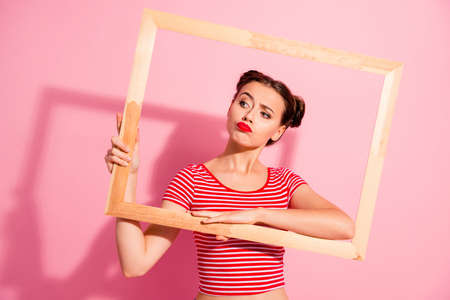 Portrait of her she nice-looking cute charming attractive glamorous bossy funny playful girl in striped t-shirt holding in hands wooden frame film movie posing isolated on pink pastel background