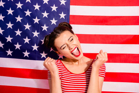 Close-up portrait of her she nice cute charming crazy glamorous shine attractive lovely cheerful cheery optimistic girl wearing striped t-shirt having fun isolated over american flag background Stock Photo