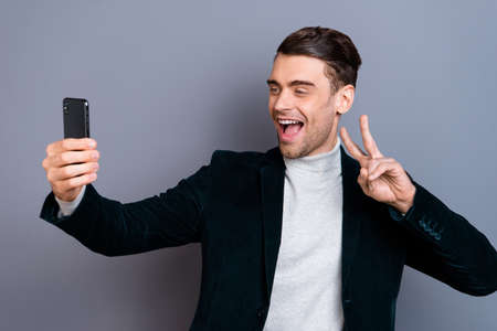 Portrait of his he nice attractive handsome bearded cheerful positive guy wearing velveteen blazer showing v-sign making taking selfie isolated over gray blue pastel background