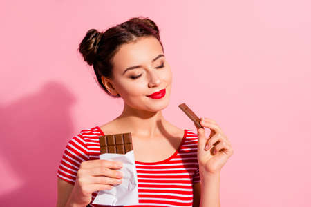 Close-up portrait of her she nice cute charming attractive winsome peaceful calm girl in striped t-shirt biting tasting desirable dessert isolated over pink pastel background