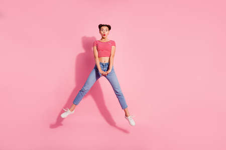 Full length body size photo shock beautiful she her lady pomade lips jump high legs separate big eyes not believe wear casual jeans denim striped red white t-shirt sit floor isolated pink background