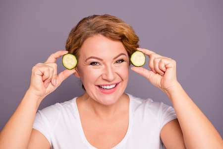 Close up photo beautiful amazing model she her lady salon spa procedures hold cucumber slices nature treatment ideal condition without under eyes bags wear white t-shirt isolated grey background