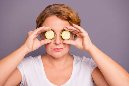 Close up photo beautiful amazing mature she her lady spa procedures hold cucumber specs slices hide eyes  nature treatment ideal condition under eyes bags wear white t-shirt isolated grey background