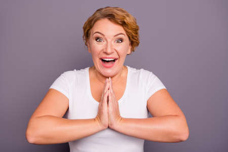 Close up photo beautiful amazing mature she her lady hands arms palms together in asking praying symbol excited glad open mouth want wish sale discount wear white t-shirt isolated grey background Reklamní fotografie
