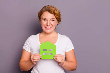 Portrait of her she nice charming attractive cheerful cheery wavy-haired lady wearing casual white t-shirt holding in hands showing green eco home isolated over gray violet purple background