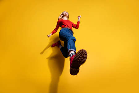 Low below angle full length body size view of nice attractive cheerful girl having fun going making step wearing vintage retro maroon boots isolated over bright vivid shine orange background