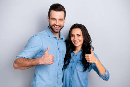 Close up portrait two beautiful amazing she her he him his couple lady guy stand close hold hands thumbs up recommend news wear casual jeans denim shirts outfit clothes isolated light grey background