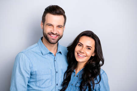 Close up portrait two cool beautiful amazing she her he him his couple lady guy friends stand close smiling camera wear casual jeans denim shirts outfit clothes isolated light grey background