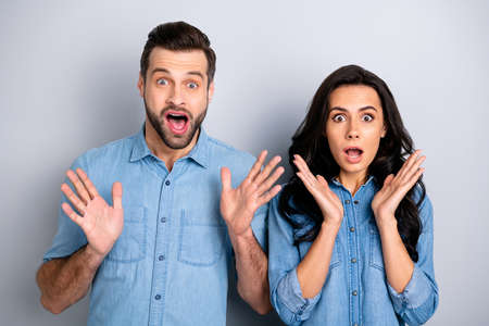 Close up portrait beautiful amazing she her he him his couple lady guy look eyes full fear hands arms raised up oh no expression wear casual jeans denim shirts outfit clothes isolated grey background