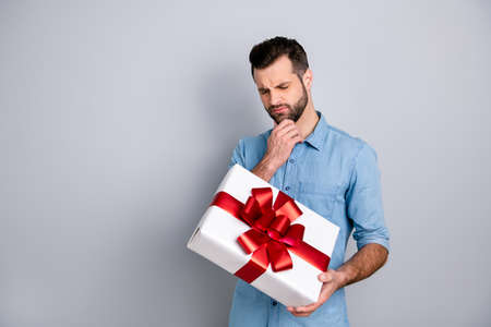 Portrait of concentrated bearded guy thinking reaction his sweetheart giftbox for 8-march touching chin by his fingers closing eyes wearing blue shirt isolated on ashy-gray background