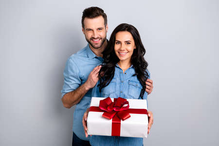 Portrait of charming handsome fellows with stubble curly hairdo holding giftbox red ribbons for 8-march 14-february days satisfied isolated on silver background wearing blue denim jackets