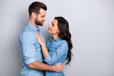 Profile side view photo of charming handsome affectionate casual spouses married delighted dressed in blue denim clothing isolated on grey background