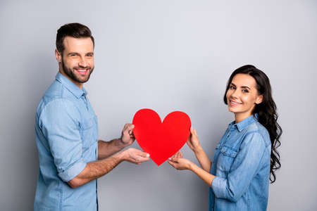 14-february Portrait of beautiful charming affectionate students showing regard respect trust support holding heart-shaped gifts presents isolated wearing blue jeans shirts on silver background