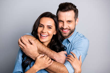 Close up photo of handsome casual joyful cute spouses  cuddling bonding placing arms around neck sharing rejoice dressed in blue denim clothing isolated on argent background