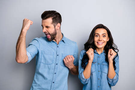 Portrait of cheerful funny impressed hipsters fellows heard incredible unbelievable news information about achievements isolated wearing blue denim clothes over silver background
