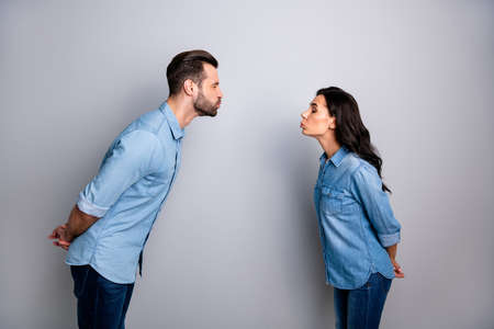 Profile side photo of funny funky handsome beloved hipsters millennial showing shyness closing eyes trying to kiss isolated on grey background wearing casual blue denim shirts