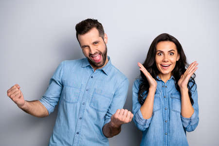 Different reactions. Portrait of delighted cheerful casual astonished students impressed by same news their goals raising fists hands dressed in blue denim clothing isolated on argent background Reklamní fotografie