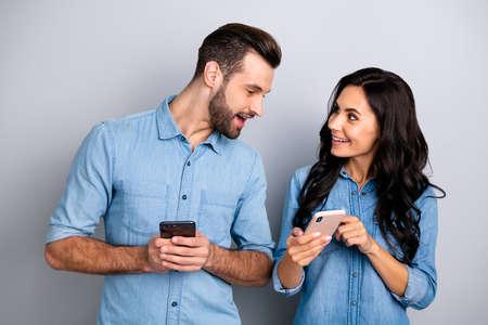 Cerca de la foto se preguntó ella ella él él su dama chico teléfono teléfono inteligente manos brazos leer lector noticias mirar interés ojos usar jeans casuales camisas de mezclilla traje ropa aislado fondo gris claro