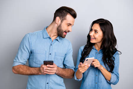 Close up photo wondered she her he him his lady guy telephone smart phone hands arms read reader news look interest eyes wear casual jeans denim shirts outfit clothes isolated light grey background