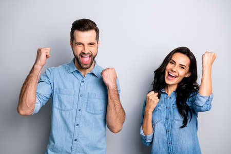 Yeah Hooray Portrait of yelling excited person students delighted impressed about their luck in lottery raising fists wearing blue denim clothing isolated on argent background Stock Photo