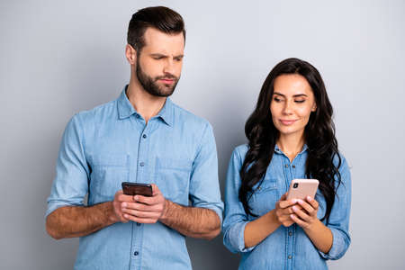 Close up photo wondered she her he him his lady guy telephone smart phone hands arms reader doubt unsure uncertain loyalty wear casual jeans denim shirts outfit clothes isolated light grey background Reklamní fotografie