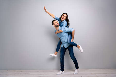 Full length body size photo funky cheer she her he him his lady guy piggyback ride walk meet adventures hand arm up run runner wear casual jeans denim shirts outfit clothes isolated grey background Stock Photo