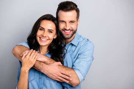 Portrait of cute adorable romantic fellows tender bonding best friends real soulmates enjoying each other placing arms around chest neck in blue denim shirts on grey background