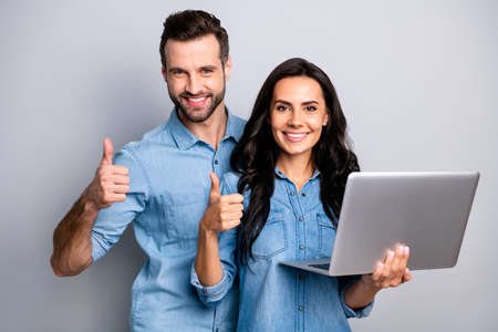 Close up photo of satisfied cheerful enjoying students fellows  isolated recommending advising products sites holding electronic device feeling positive wearing denim jackets on grey background