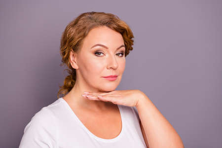 Close-up portrait of nice charming attractive content groomed wavy-haired lady wearing casual white t-shirt holding palm under chin flawless face isolated on gray violet purple pastel background