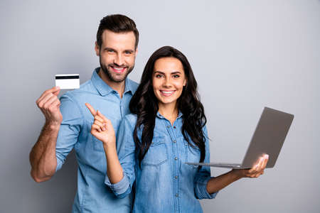Close up photo beautiful amazing she her he him his couple lady guy hold credit card notebook show simple way internet buy pay  wear casual jeans denim shirts outfit clothes isolated grey background