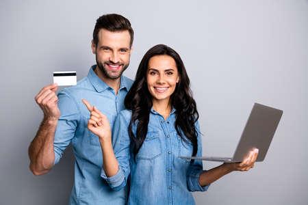 Cerrar foto hermosa increíble ella ella él él su pareja dama chico sostener tarjeta de crédito cuaderno mostrar manera simple internet comprar pagar usar pantalones vaqueros casuales camisas de mezclilla traje ropa aislado fondo gris