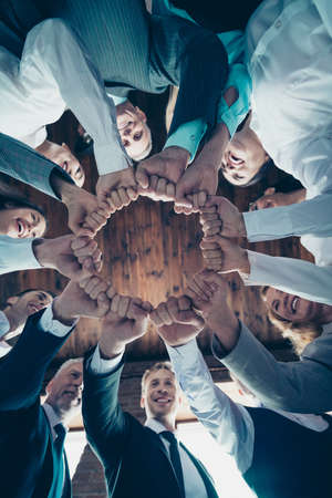 Vertical low angle view photo business people round circle she her he him his hold hands arms fists together celebrate project prize nomination power inspiration all dressed formal wear jackets shirts Stock Photo