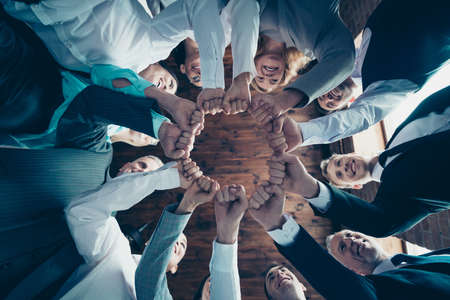 Close up low angle view photo diversity members business people circle she her he him his hold hands arms fists together celebrate project nomination power inspiration formal wear jackets shirts