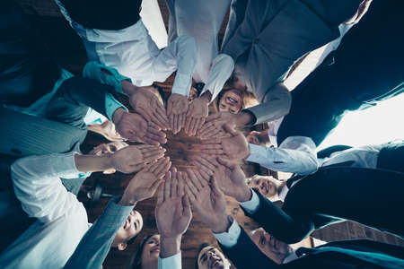 Close up low angle view photo diversity members business people circle she her he him his hold both hands arms together best brigade having party project nomination power formal wear jackets shirts