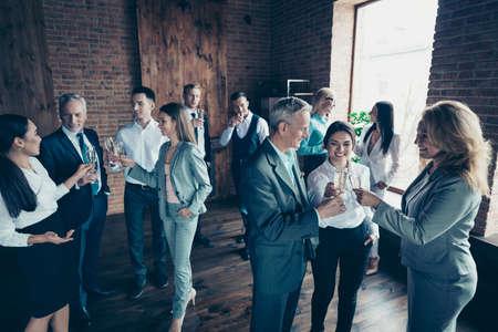 Gros plan photo les gens d'affaires foule différents âges course loisirs excité team building membres la rassemblant elle il lui sa boisson au vin d'or dire toasts félicitations tenues de soirée vestes chemises Banque d'images
