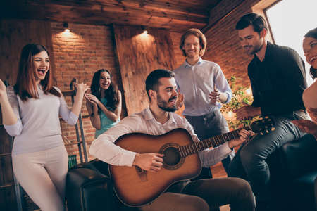 Close up photo gathering best friends buddies hang out vocal soloist play guitar old songs rest relax she her ladies he him his guys wear dresses shirts formal wear sit sofa loft room indoors