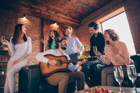 Close up photo pleasant serenate long waited gathering best friends buddies hang out vocal soloist play guitar she her ladies he him his guys wear dress shirts formal wear sit sofa loft room indoors Stock Photo