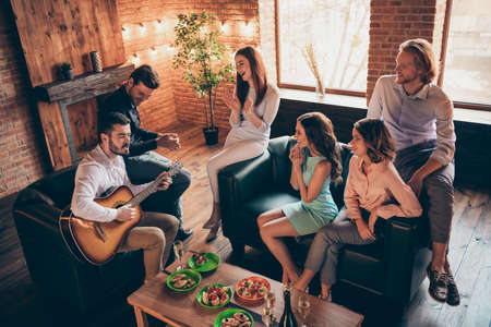 Close up photo having fun gathering best friends buddies hang out vocal soloist play guitar perform new song she her ladies he him his guys wear dresses shirts formal wear sit sofa loft room indoors Stock Photo