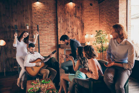 Close up photo having fun gathering best friends buddies hang out vocal soloist play guitar rock roll legends she her ladies he him his guys wear dresses shirts formal wear sit sofa loft room indoors